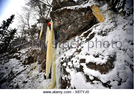 Woman ice climber ascends a large icefall in Southcentral Alaska - Stock Photo