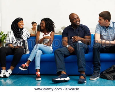 Male lecturer chatting to students in college - Stock Photo