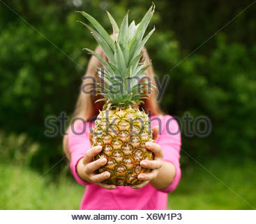 Young woman holding pineapple in her hands, Debica Poland - Stock Photo