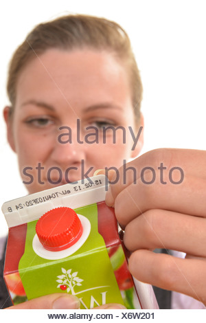 Woman checking the best before or use-by date on a drinks carton - Stock Photo