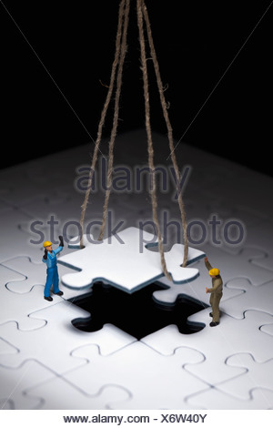 Miniature workmen guiding a hanging puzzle piece into place - Stock Photo
