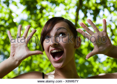 young woman with brackets makes a face - Stock Photo