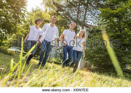 Group of people walking through forest - Stock Photo