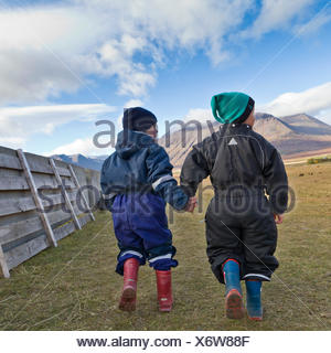 Children holding hands in the countryside at a horse gathering in Iceland.  Annual Horse Round Up-Laufskalarett, Skagafjordur, Iceland. - Stock Photo