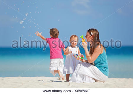 mother sitting with her two children on the beach and blowing bubbles - Stock Photo