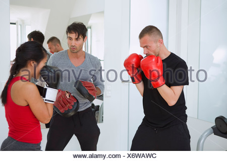 Trainer working with boxers in gym - Stock Photo