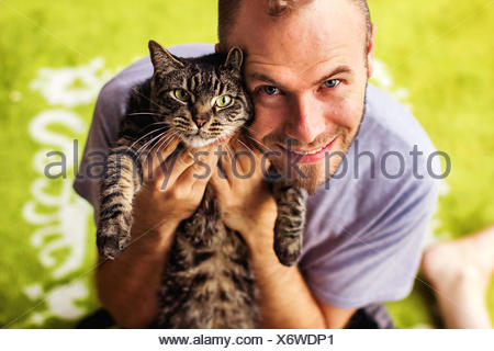 Portrait of man with tabby cat - Stock Photo