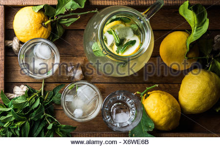 HOMEMADE LEMONADE WITH MINT, ICE AND FRESH LEMONS served with fresh lemons and mint on wooden tray background, top view - Stock Photo