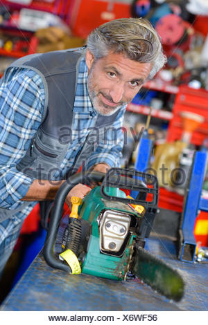 Portrait of mechanic working on chainsaw - Stock Photo