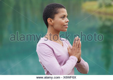 portrait of african american woman in yoga pose outdoors - Stock Photo