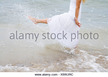 Young woman playing water with feet low section - Stock Photo