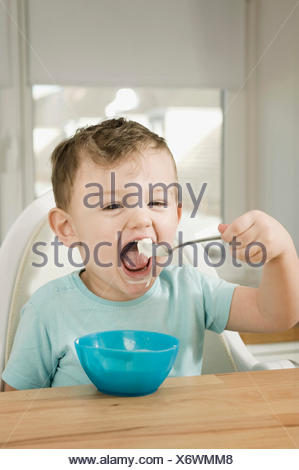 Portrait of boy eating pap - Stock Photo