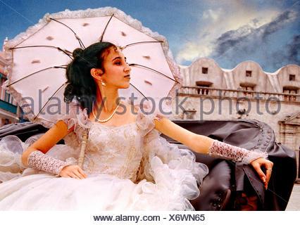 Cuban woman sitting in chariot, wearing white skirt, holding sun shade, Cuba - Stock Photo