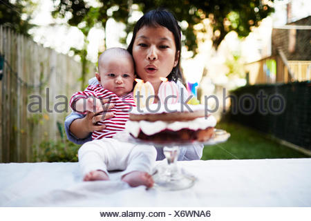 Mother holding baby son, blowing out candles on cake - Stock Photo