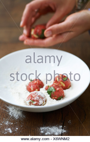 Rolling the meatballs in the flour - Stock Photo