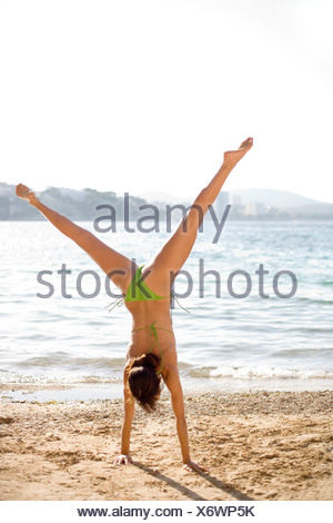 Woman exercising. Performing a hand-stand on a beach. - Stock Photo