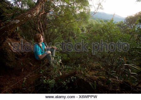 A girl watches the sunrise from Mossy Rock, a high point on the ridge in Gunung Palung National Park. - Stock Photo