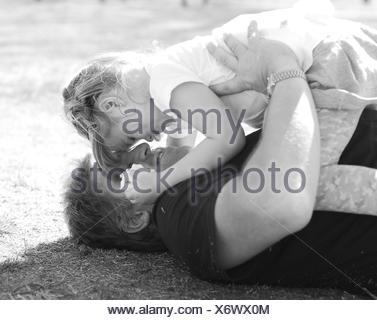 Father lying on the grass playing with his daughter - Stock Photo