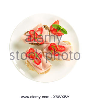 Open faced ham sandwiches garnished with red pepper - Stock Photo