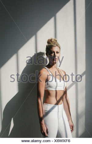 Portrait of a blonde woman, in a white crop top and leggings, standing in front of a white wall, posing for a picture. - Stock Photo
