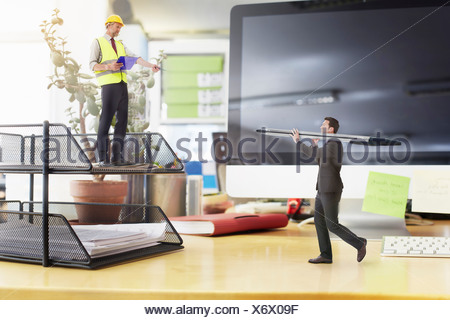 Mature foreman directing businessman carrying large pen on oversized desk - Stock Photo