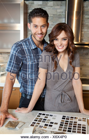 Portrait of beautiful young couple standing in model home kitchen with tile color samples - Stock Photo