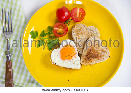 Fried egg in heart shape, toasts, cherry tomatoes on yellow plate - Stock Photo