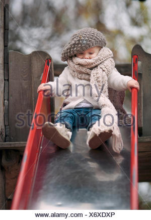 Portrait of little girl wearing big scarf and woolly hat on a slide - Stock Photo