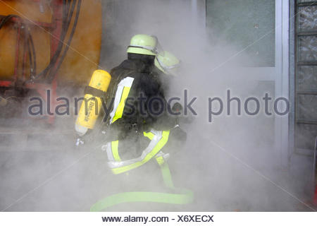 firefighting exercise with protective respiratory equipment, Germany - Stock Photo