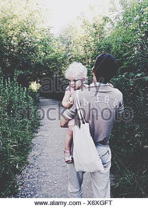 Rear View Of Man Holding Baby And Bag Walking On Walkway Amidst Trees In Park - Stock Photo