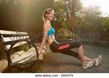 Female runner stretching against park bench - Stock Photo