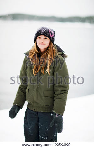 Sweden, Stockholm, portrait of girl (12-13) wearing winter coat and hat on waters edge - Stock Photo
