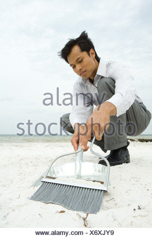 Man crouching on beach, sweeping sand into dustpan, low angle view - Stock Photo