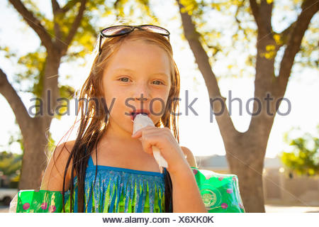 Portrait of girl eating ice lolly in garden - Stock Photo