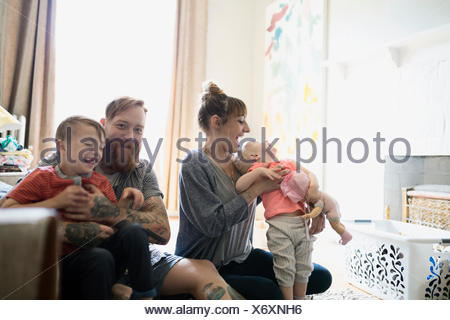 Happy young family in living room - Stock Photo