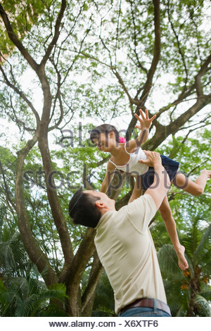 Mid adult man tossing his daughter in air, Singapore - Stock Photo