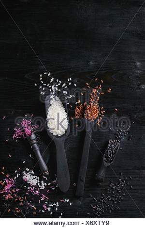 Variety assortment of raw uncooked colorful rice white, black, brown, pink in black spoons and scoop over burnt wooden background. Top view with space - Stock Photo