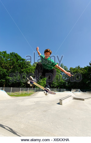 Germany, Duesseldorf, Young man performing tricks with skateboard in skatepark - Stock Photo