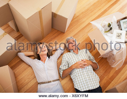 Happy couple laying on floor of new house - Stock Photo