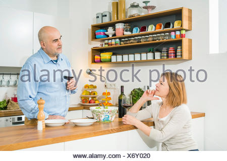 Senior couple talking in kitchen - Stock Photo