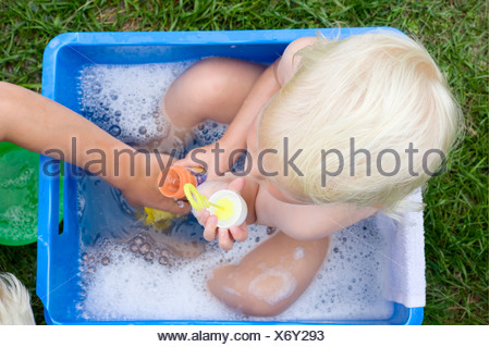 A little girl sitting in a plastic box and being bathed, Brittany, France, Europe - Stock Photo