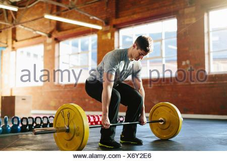 Man lifting weights in gymnasium - Stock Photo