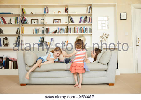 Woman reclining on sofa while daughters read storybook - Stock Photo