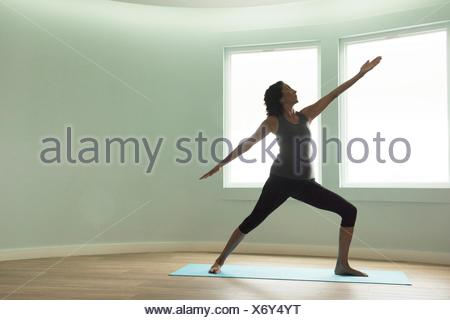 Mature woman doing yoga warrior pose in curved room - Stock Photo