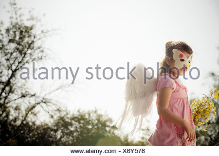Girl in angel wings and face mask - Stock Photo