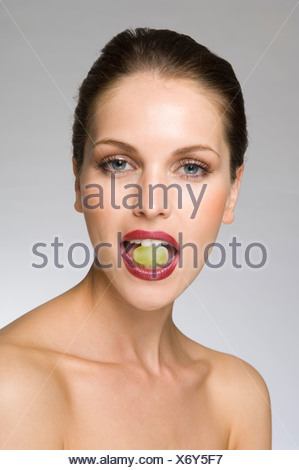 female beauty with grape in mouth - Stock Photo