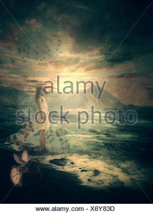 Girl standing on beach looking out to sea - Stock Photo