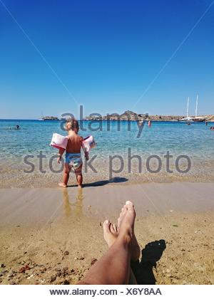 Cropped Legs Of Man In Front Of Child Wearing Water Wings By Sea Against Sky - Stock Photo