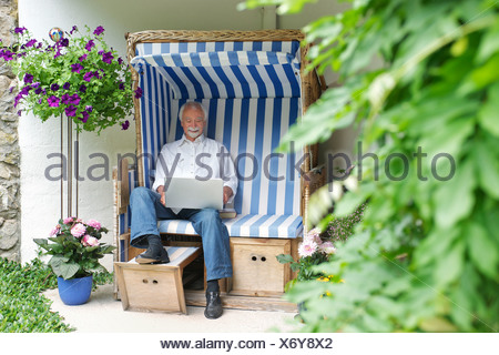 Senior man using laptop on garden seat - Stock Photo