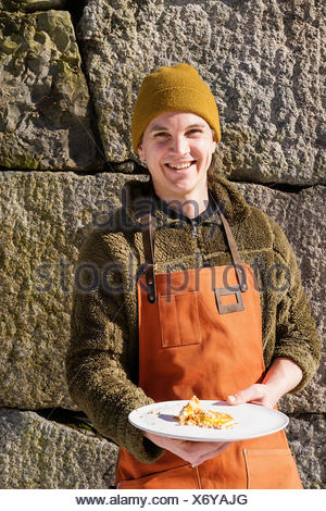 Sweden, Vastmanland, Man with dish - Stock Photo